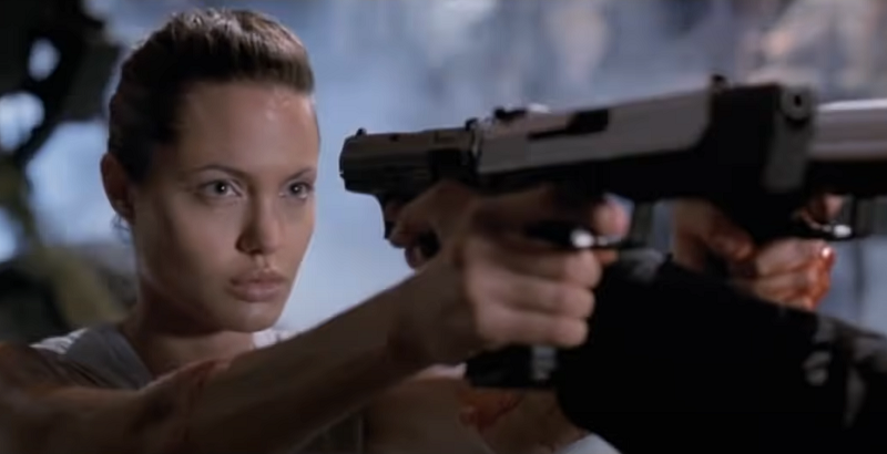 Lara Croft aiming two pistols while also being aimed at
