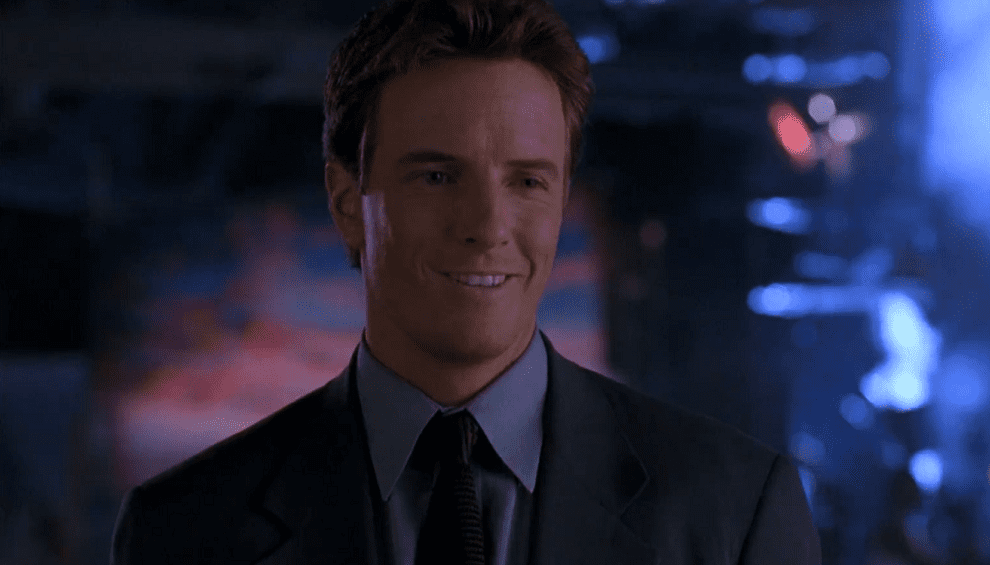 Linden Ashby's Johnny Cage smiling in a grey suit