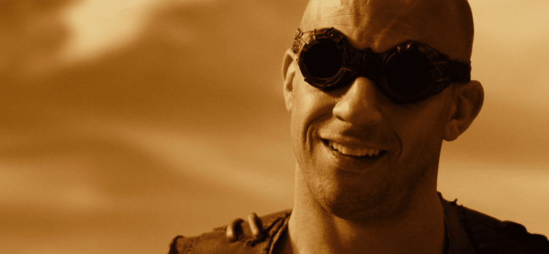 Vin Diesel Riddick smiling in the desert with goggles
