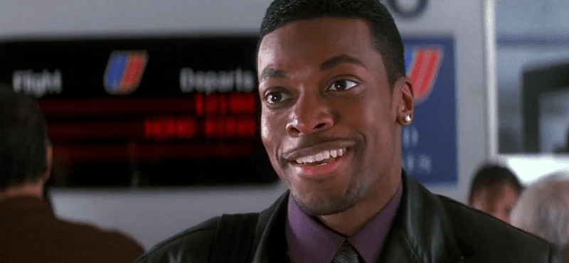 Chris Tucker as Carter smiling in an airport