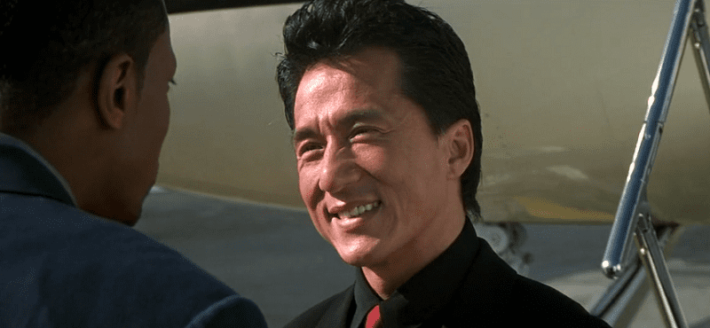 Jackie Chan as Lee smiling at Carter near airplane
