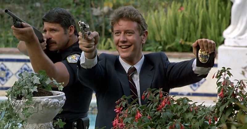 Billy Rosewood holding a gun and badge while smiling