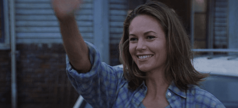 Diane Lane waving and smiling in front of a house