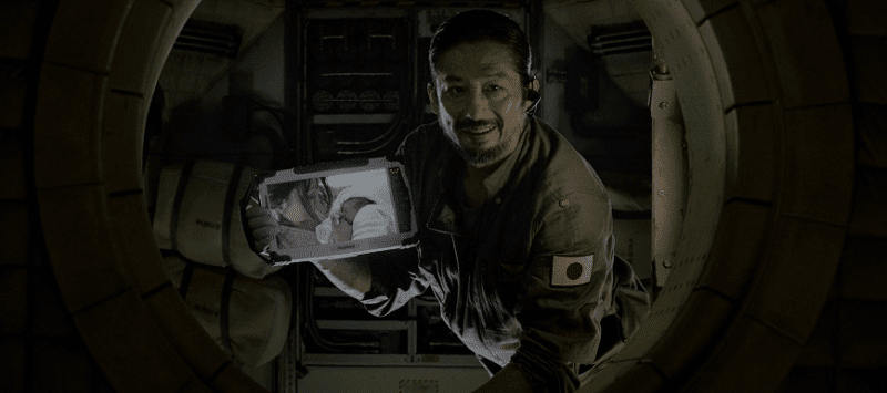 Hiroyuki Sanada holding a tablet showing his family while smiling