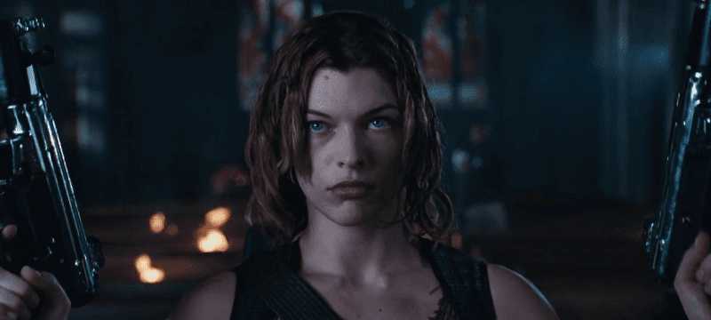 Milla Jovovich as Alice holding two MP5s in a church
